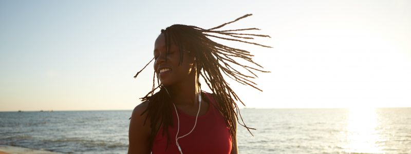 Happy smiling young Black woman dancing and jumping on beach to the music in her earphones